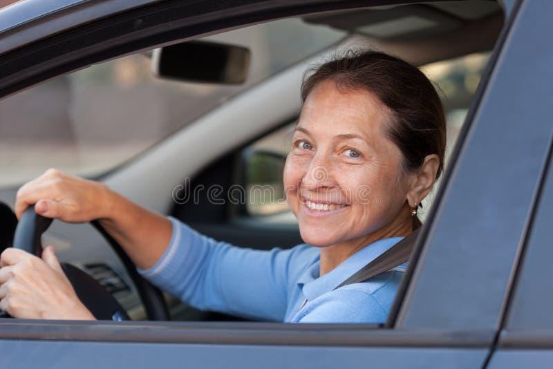 Elderly woman in car. Mature woman driving black car stock image