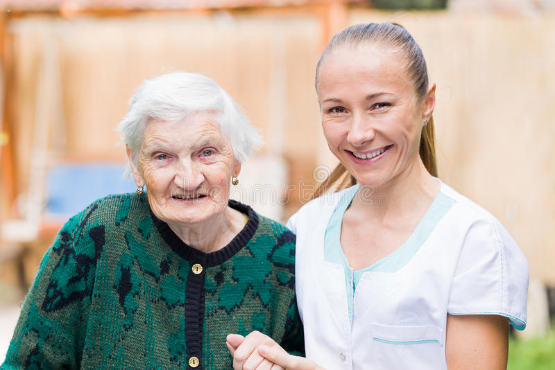 Elderly woman with caregiver. Photo of elderly women with her caregiver royalty free stock photography