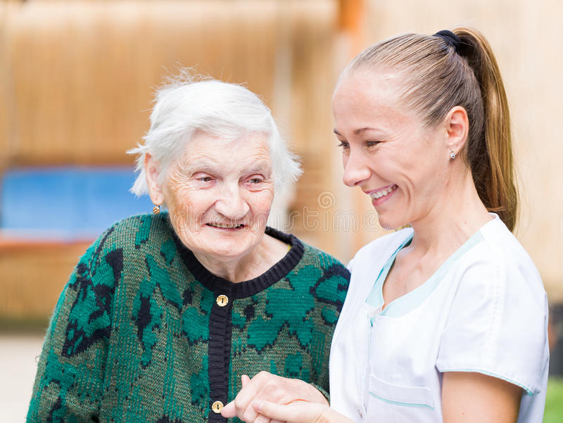 Elderly woman with caregiver stock image