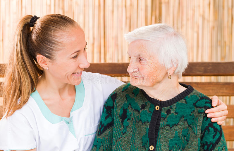 Elderly woman with caregiver. Photo of elderly women with her caregiver stock image