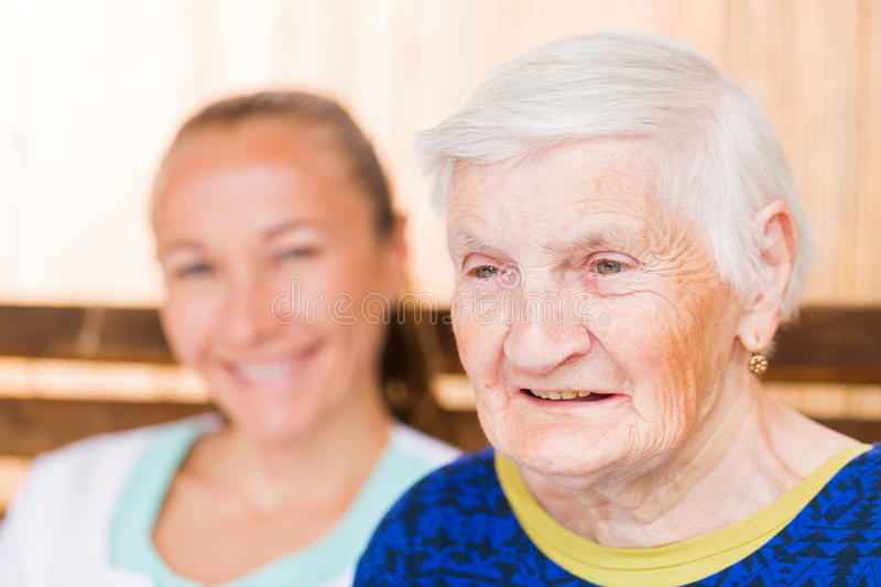 Elderly woman with caregiver. Photo of elderly women with her caregiver royalty free stock photo