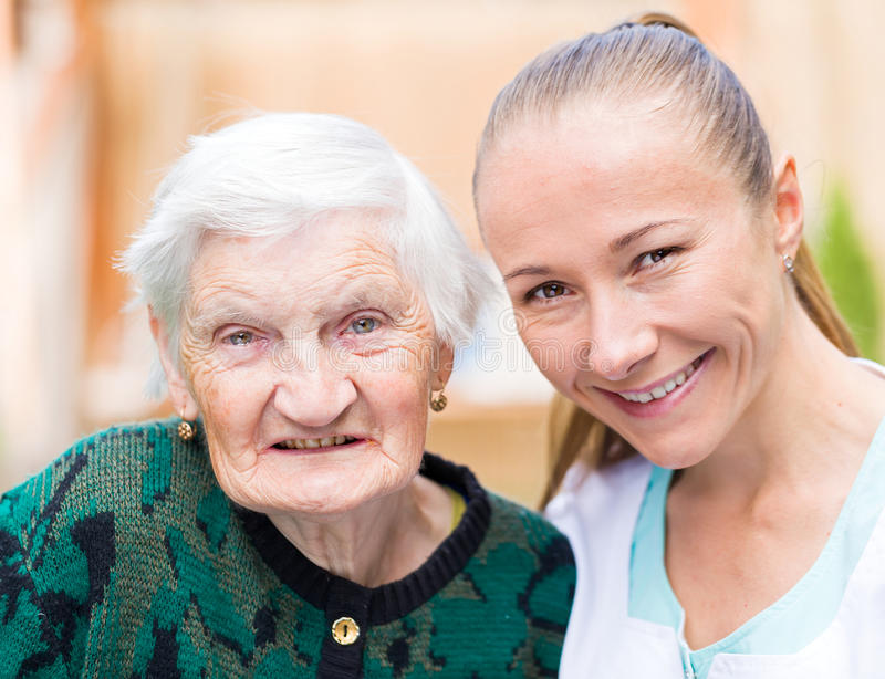 Elderly woman with caregiver. Photo of elderly women with her caregiver stock photography
