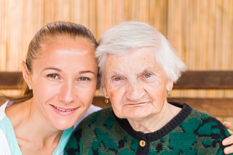 Elderly woman with caregiver. Photo of elderly women with her caregiver stock photos