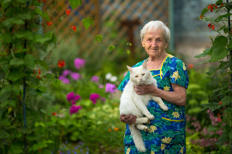 Elderly woman with a cat in hand is worth in the garden. Happy. royalty free stock photo