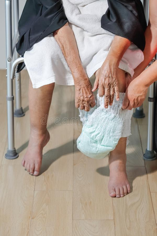 Elderly woman changing diaper with caregiver. Close up elderly women changing diaper with caregiver royalty free stock photography