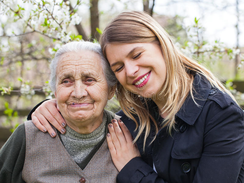 Elderly woman with cheerful caregiver outdoor, springtime royalty free stock photos