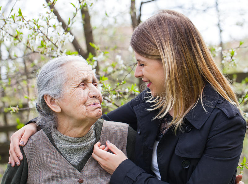 Elderly woman with cheerful caregiver outdoor, springtime stock images