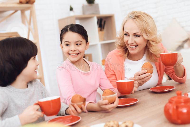 Elderly woman with cheerful grandson and granddaughter eating cookies and drinking tea in red mugs at kitchen. stock photo