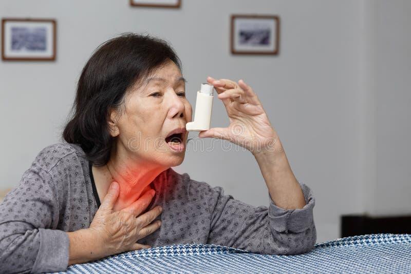 Elderly woman choking and holding an asthma spray stock photo