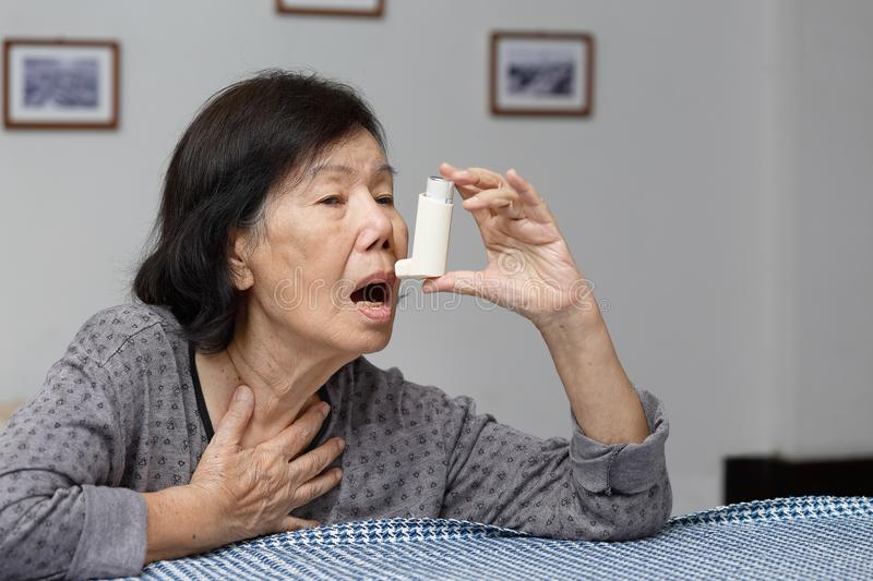 Elderly woman choking and holding an asthma spray stock image