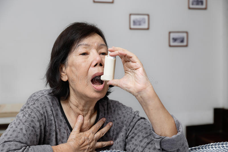 Elderly woman choking and holding an asthma spray stock photography