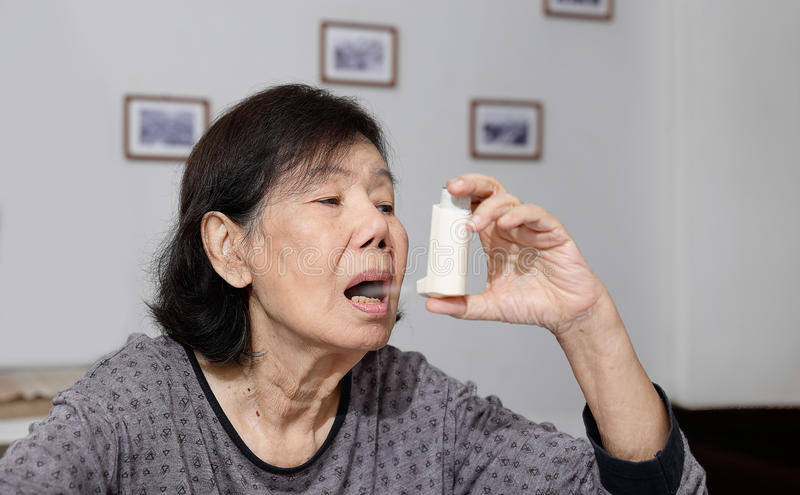 Elderly woman choking and holding an asthma spray stock images