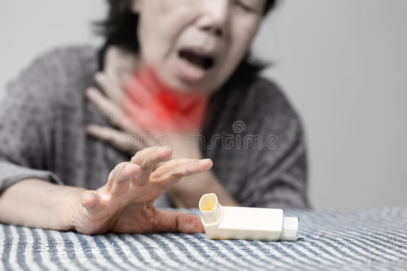 Elderly woman choking and holding an asthma spray royalty free stock photography