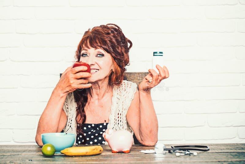 Elderly woman choose apple or pill bottle stock photos