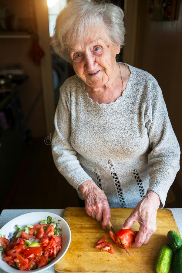 An elderly woman chops vegetables for a salad. Vegetable. royalty free stock images