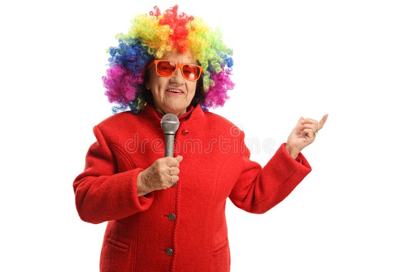 Elderly woman with a clown wig and a microphone royalty free stock images