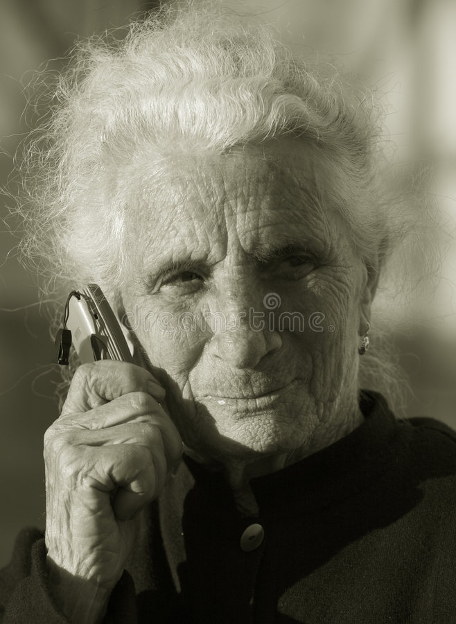 Elderly woman communicating. Duotone of Elderly woman using a portable telephone royalty free stock images