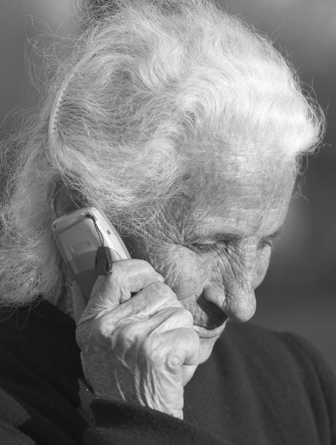 Elderly woman communicating 2. Elderly woman using a portable telephone stock image