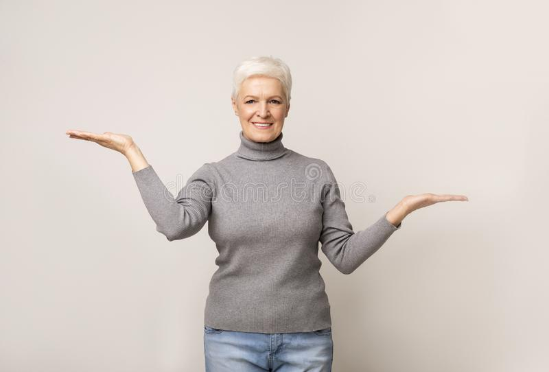 Elderly woman comparing variants, making scales with her empty hands stock photos
