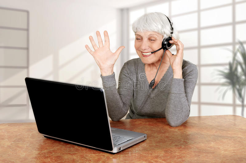 Elderly woman at the computer communicates royalty free stock photos