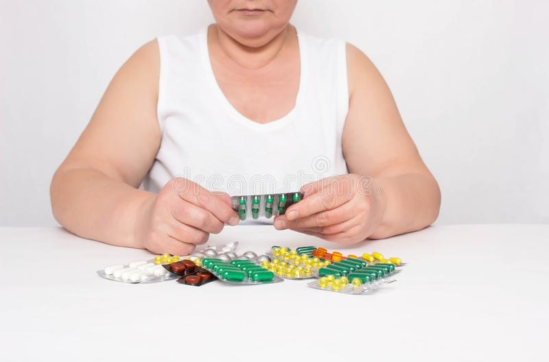 An elderly woman is considering a bunch of pills that lie on the table, the concept of healing and taking synthetic vitamins and royalty free stock image