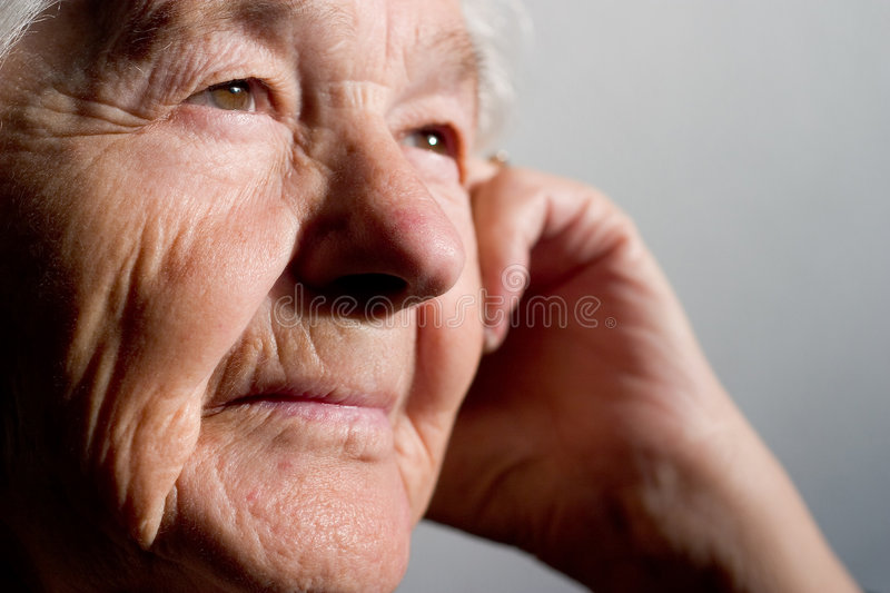 Elderly woman contemplating stock photos