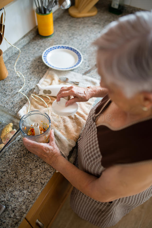 Elderly woman cooking in the kitchen royalty free stock image