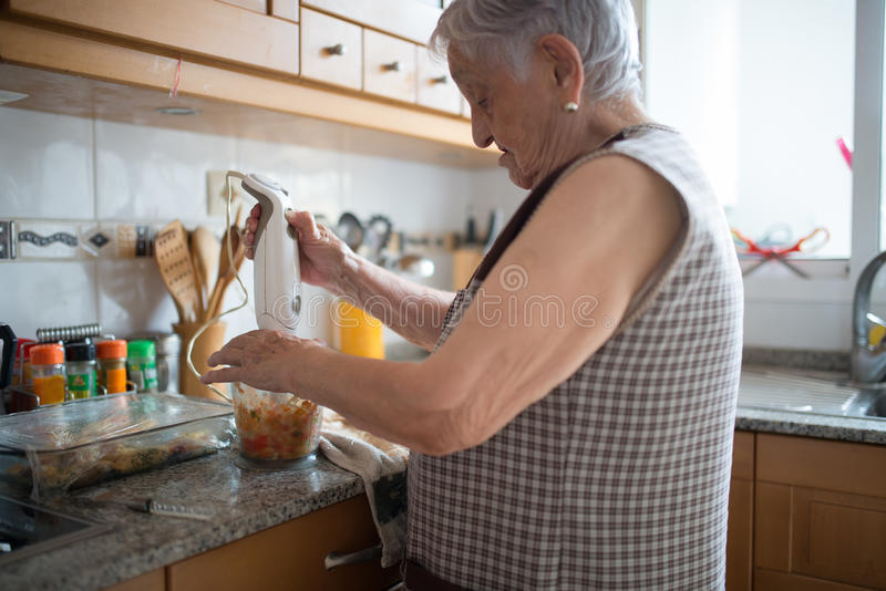 Elderly woman cooking royalty free stock image