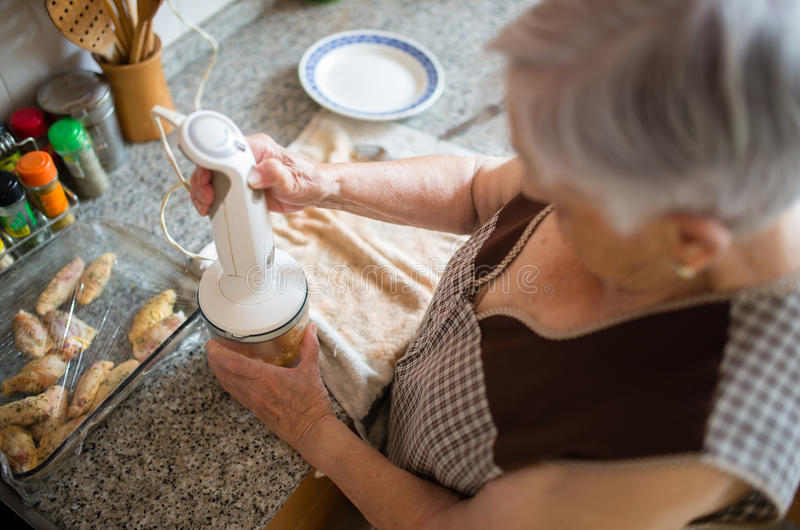 Elderly woman cooking in the kitchen stock image