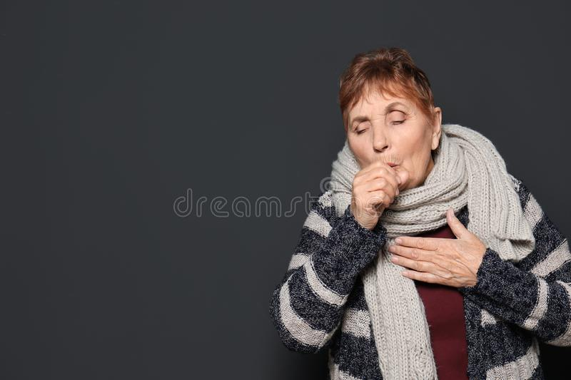 Elderly woman coughing against dark background. Space for text royalty free stock photography