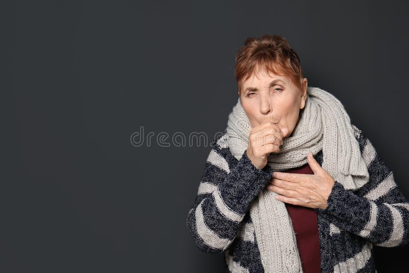 Elderly woman coughing against dark background. Space for text royalty free stock photos