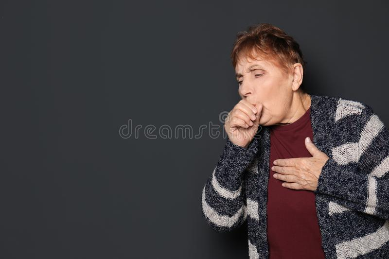 Elderly woman coughing against dark background. Space for text stock image