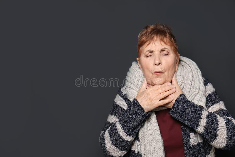 Elderly woman coughing against dark background. Space for text stock photography