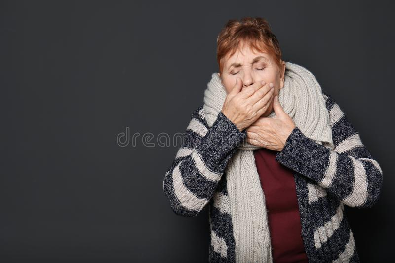 Elderly woman coughing against dark background. Space for text stock photo