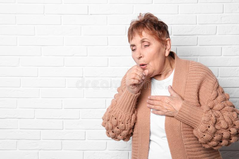 Elderly woman coughing near brick wall. Space for text royalty free stock image