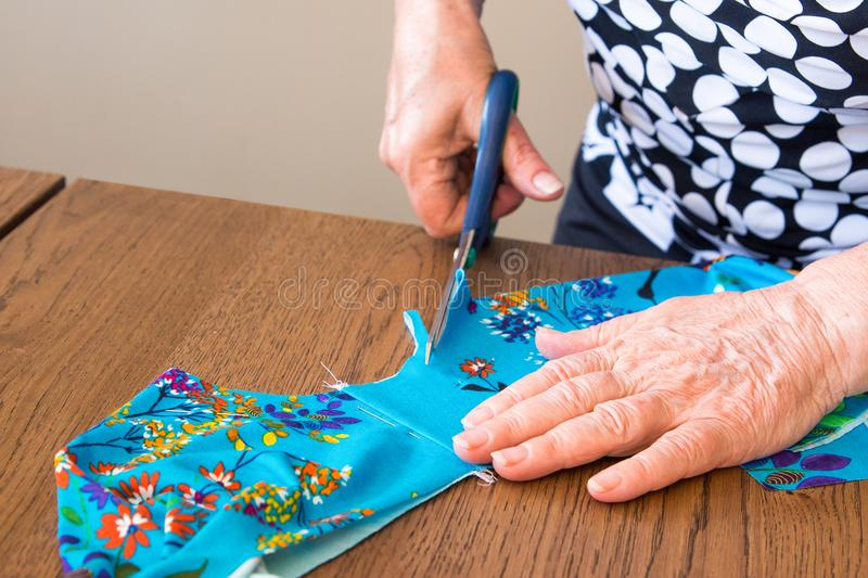Elderly woman cuts out a piece of fabric for a dress. A woman cuts a piece of cloth with a pair of scissors on a table for a child`s dress stock photography
