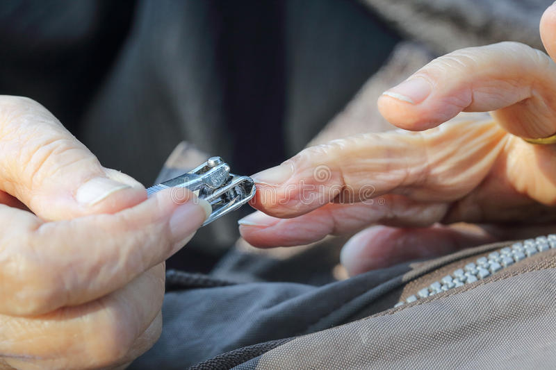 Elderly woman cutting nails royalty free stock image