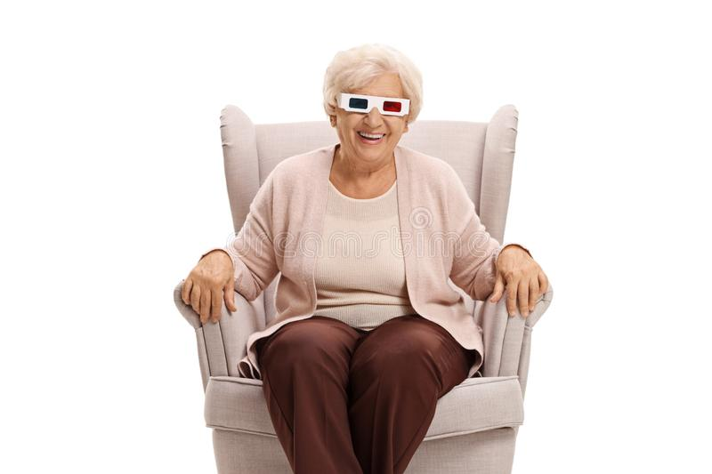 Elderly woman with 3D glasses sitting in an armchair. Isolated on white background stock photos