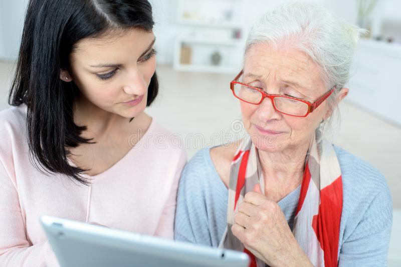 Elderly woman and daughter reading their tablet royalty free stock photo