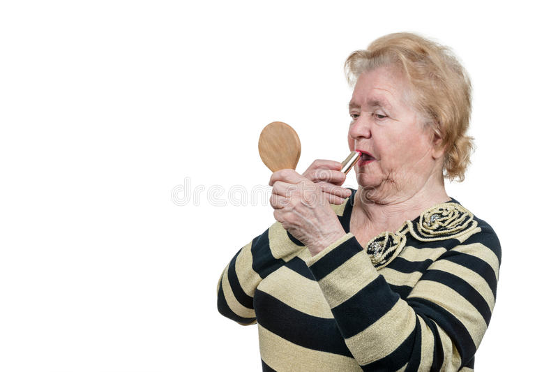Elderly woman does a make-up stock photos