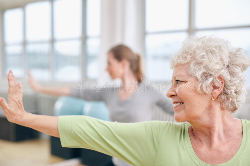 Elderly woman doing stretching workout at yoga class royalty free stock photos