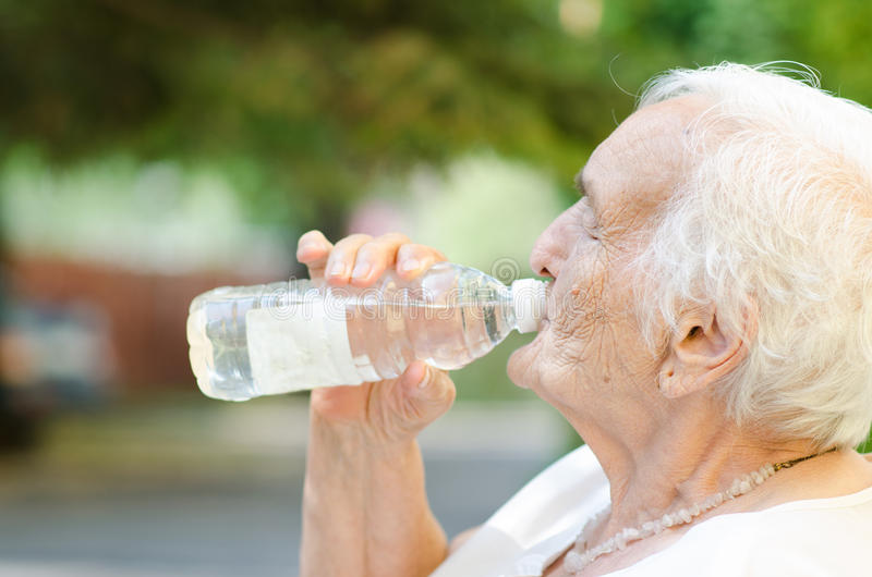 Elderly woman drinking water stock photo