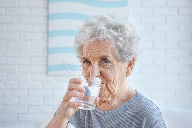 Elderly woman drinking water at home. stock photography