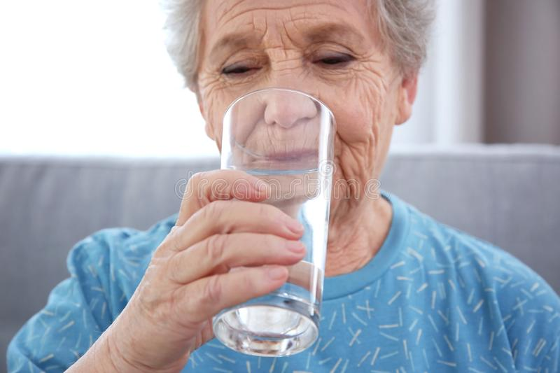 Elderly woman drinking water at home. royalty free stock photos