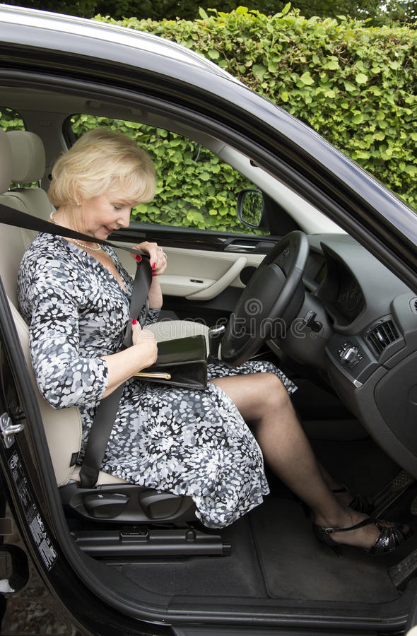 Elderly woman driver fastening self belt in a car royalty free stock photos