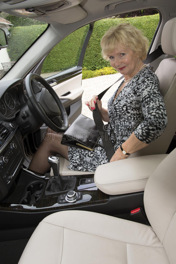 Elderly woman driver fastening self belt in a car stock image