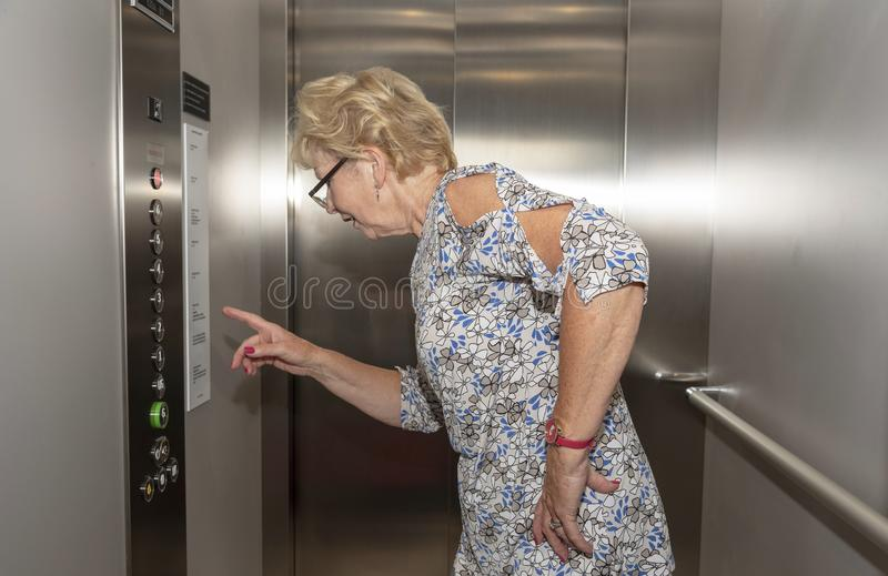 Elderly woman in a elevator stock photos