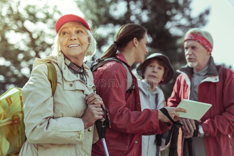 Elderly woman enjoying hiking with the group of tourists royalty free stock photography