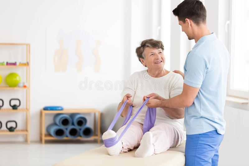 Elderly woman exercising with band. Elderly women exercising her leg with a stretch band with assistance of a young physiotherapist royalty free stock photography