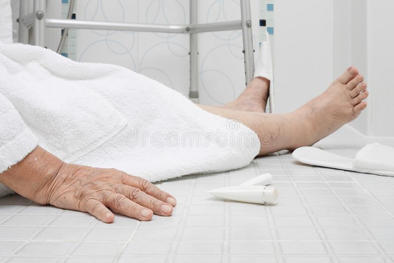 Elderly woman falling in bathroom stock images
